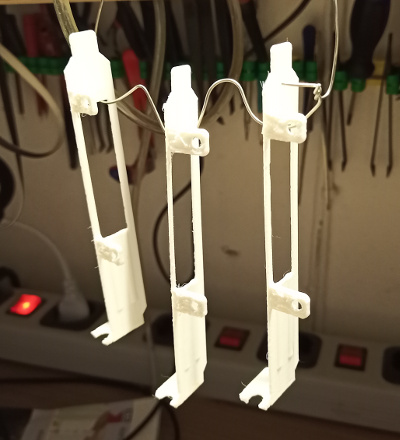 Three 3D printed slot covers hanging on a wire